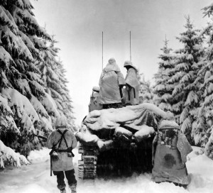 Tanks and Infantrymen of the 82nd Airborne Division, Company G, 740th Tank Battalion, 504th Regiment, push through the snow toward their objective in Belgium.