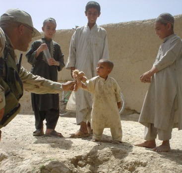 Soldier gives an Afghan child his first stuffed animal.