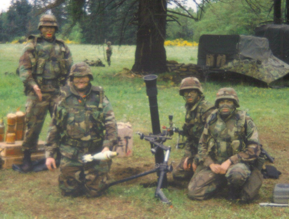 photo: four soldiers by a mortar tube. One hold a mortar round.